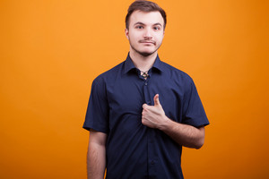 Handsome young man showing thumb up on yellow background. Everething will be OK