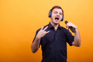 Handsome young man singing rock music with his headphones over yellow background. Great music