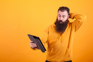 Handsome young man with long beard looking confused at tablet over yellow background. Handsome man.