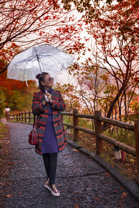 happiness asian woman with rain umbrella standing in leaves color change  japan autumn season