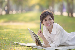 happiness emotion relaxing time of asian younger woman with book and pen in summer park