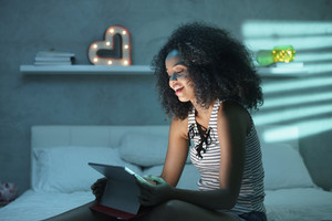 Happy african american teenager in bed at home with tablet. Young black woman watching movie in bedroom at night and laughing.