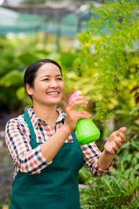 Happy Asian woman spraying water on plants in the garden