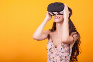 Happy beautiful girl wearing virtual reality goggles in studio over yellow background. VR 360 gaming technology.