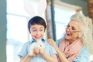 Happy boy with rabbit and his grandmother laughing