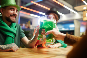 Happy buddies toasting with green beer over table