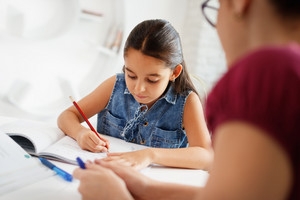 Happy caucasian family at home. Hispanic mother and female child. Latina mom helping daughter with school homework. Education, people, motherhood and relationship, woman teaching and girl learning