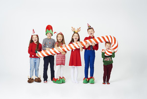 Happy children holding huge candy cane