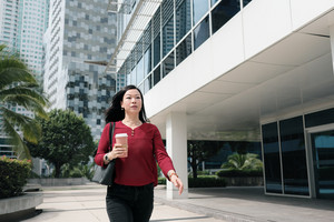 Happy Chinese female manager commuting and holding coffee cup. Confident Asian businesswoman in late walking quickly to office in the morning.