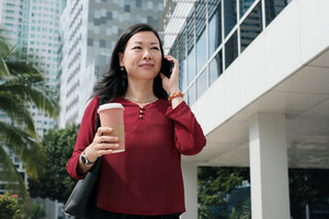 Happy Chinese female manager talking on cell phone and holding coffee cup. Confident Asian businesswoman walking to office in the morning.