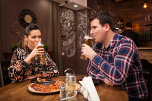 Happy couple drinking beer and eating pizza. Casual time.