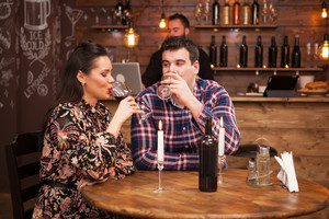 Happy couple drinking wine when having date in restaurant. Beautiful couple.