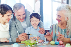 Happy family painting Easter eggs together