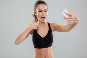 Happy fitness woman making selfie on her smartphone, winks and showing thumb up over gray background