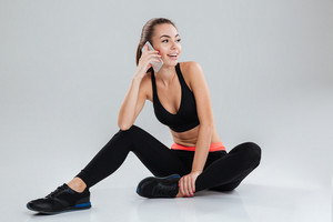 Happy fitness woman sitting on the floor and looking away while talking on her smartphone over gray background