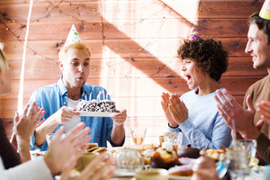 Happy friends congratulating young man blowing candles on birthday cake by festive table