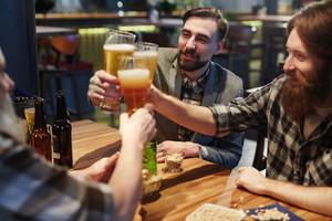 Happy friends having beer in pub