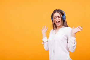 Happy girl wearing blue headphone and singing over yellow background. Having fun
