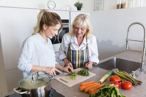 Happy grandmother and her granddaughter cooking together on a kitchen at home