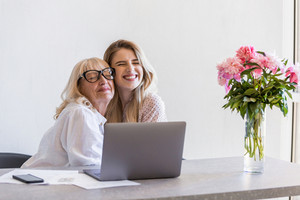 Happy grandmother hugging her young granddaughter while sitting at the table with laptop computer indoors