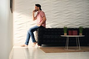 Happy hispanic man talking on cell phone at home. Latino guy speaking with mobile telephone and laughing