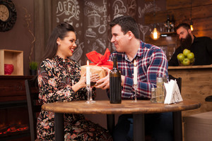 Happy husband giving wife a present in a hipster pub. Beautiful relationship.