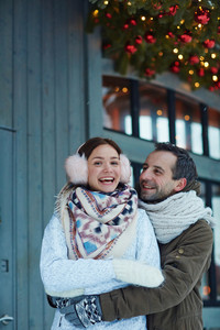 Happy man embracing his laughing wife on xmas eve outdoors