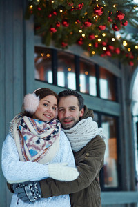 Happy man embracing his wife on winter day