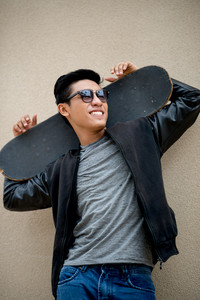 Happy man in sunglasses holding a skateboard: outdoor lifestyle portrait