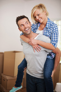 Happy man picking up his wife in their new home