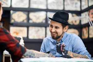 Happy master of tattooing and his customer talking in salon