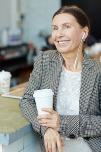 Happy mature woman with earphones having coffee break