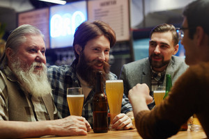 Happy men with beer spending traditional Irish holiday in pub