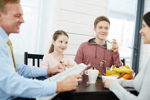 Happy middle-aged parents and their children starting new day with delicious breakfast, handsome father reading newspaper, waist-up portrait