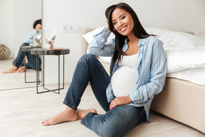 Happy pregnant asian woman leaning on a sofa while sitting on the floor at home