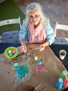Happy retired female looking at camera while painting eggs