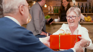 Happy senior woman when she's receiving a red gift box from her husband during their date. Cheerful senior couple. Couple smiling.