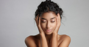 happy serene young woman with beautiful olive skin and curly hair ideal skin and brown eyes