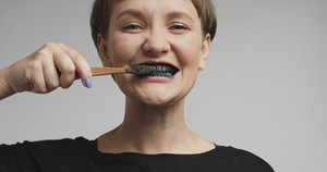 Happy smiling attractive young woman brushing her teeth with black toothpaste and having fun