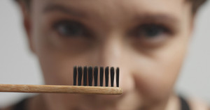 Happy smiling attractive young woman looking on a toothbrush closeup
