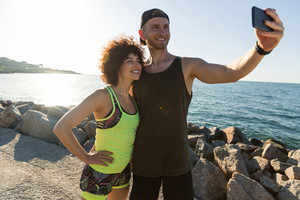 Happy smiling fitness couple in sportswear taking a selfie while standing together outdoors