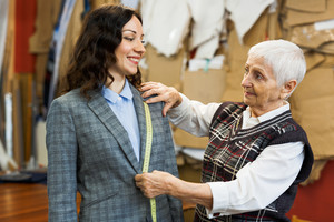 Happy tailor and her client talking during taking measures
