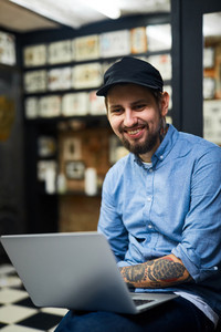 Happy tattooist with laptop working in the net