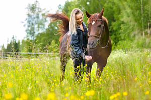 Happy woman feeding her arabian horse with snacks in the field