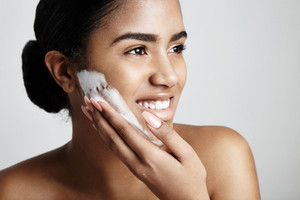 happy woman wash her face with a soap foam