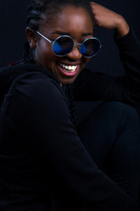 Happy Woman Wearing Sunglasses Over Black Background