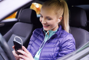 Happy woman with phone in the car
