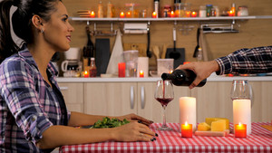 Happy young couple having romantic dinner at their new flat. Sweet couple.