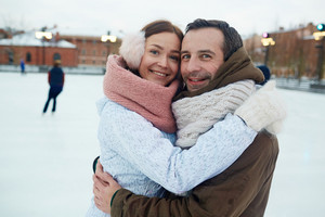 Happy young couple in winterwear embracing on skating-rink