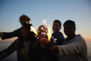 Happy young friends with sparklers in hands having fun at night beach party, picturesque seascape on background